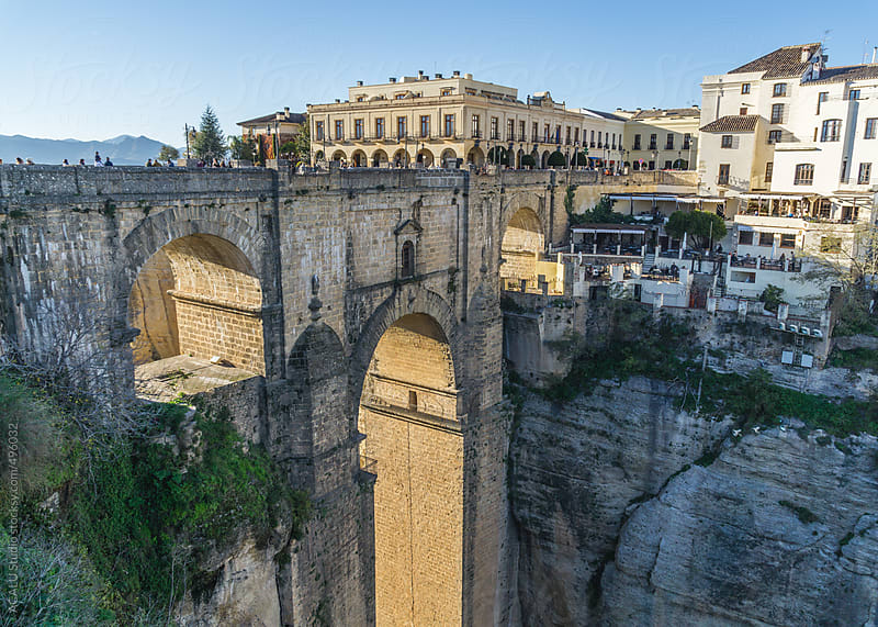People walking on bridge El Tajo Gorge in Ronda city by ACALU Studio for Stocksy United