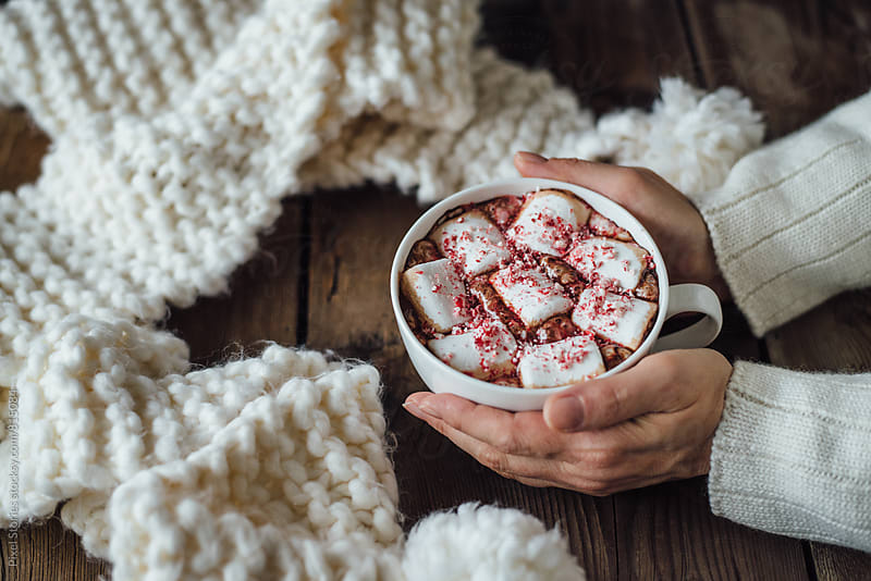 Woman holding marshmallow hot cocoa cup by Pixel Stories for Stocksy United