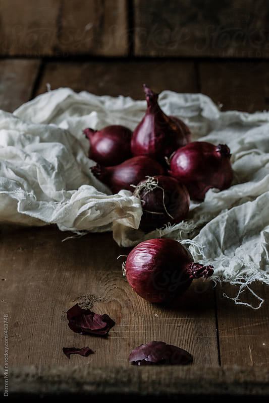 Red onions in rustic setting. by Darren Muir for Stocksy United