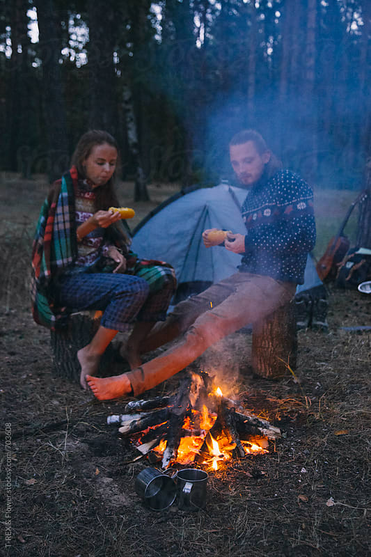 Couple of travelers eating corn near bonfire by Danil Nevsky for Stocksy United
