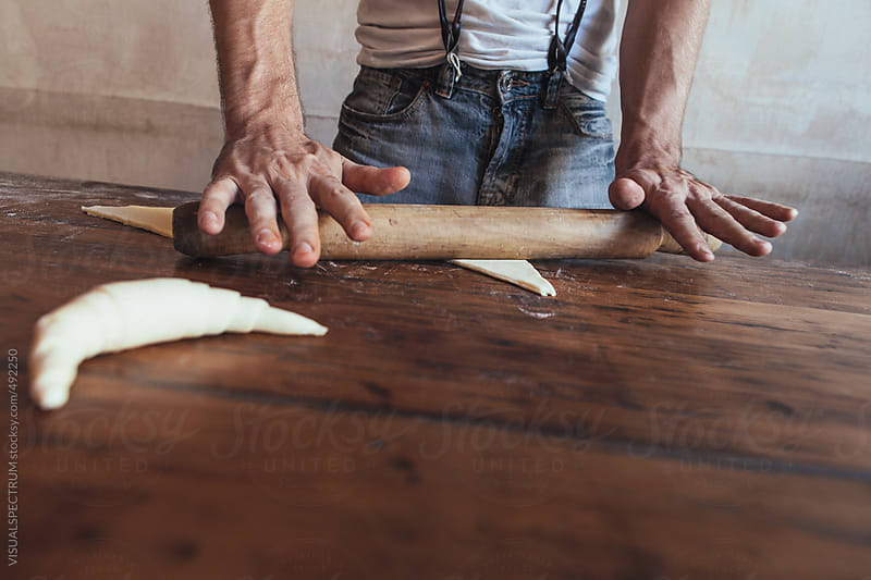 Young Male Artisan Baker Using Rolling Pin and Making Croissants on Rustic Wood Table by VISUALSPECTRUM for Stocksy United