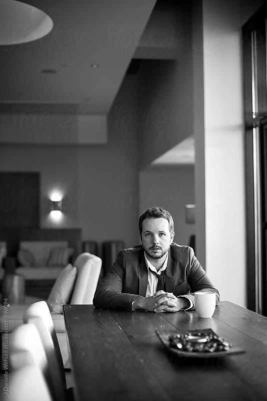 Business man sitting at end of long table with coffee cup by J Danielle Wehunt for Stocksy United