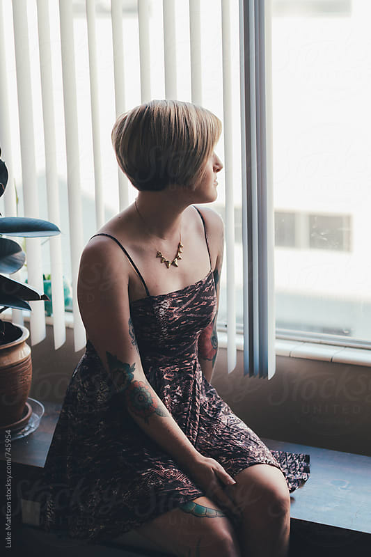 Young Tattooed Blonde Woman Wearing Dress Sitting On Bench By Window by Luke Mattson for Stocksy United