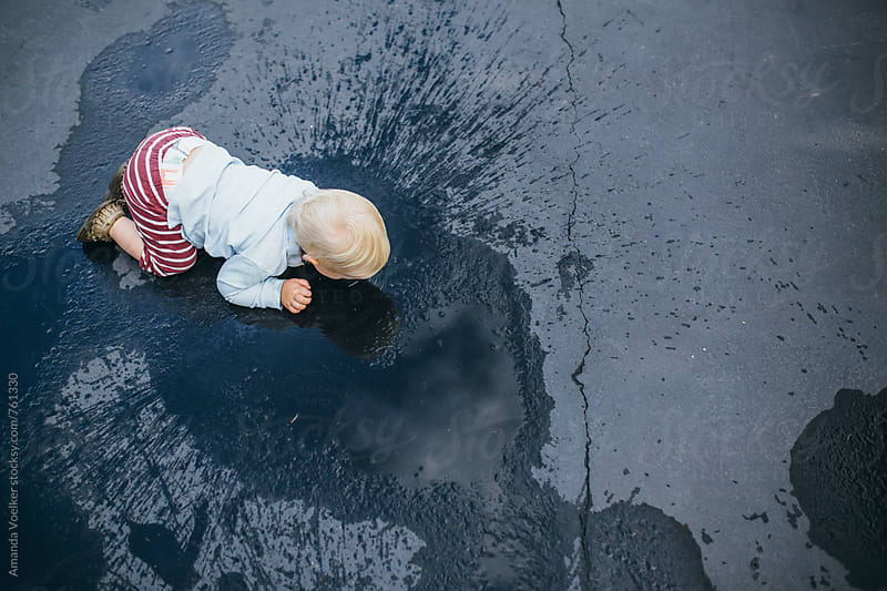 Birds Eye View of  Toddler Boy Crawling Through Puddles by Amanda Voelker for Stocksy United