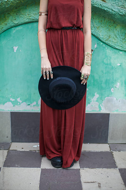 Beautiful young woman in red dress with blue hair and a hat by Maja Topcagic for Stocksy United