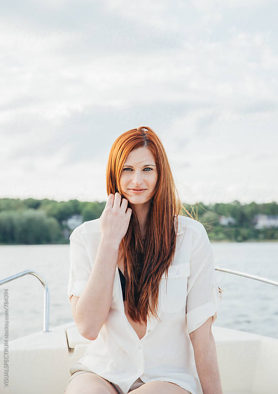 Portrait of Red-Haired Young Woman Sitting on Motorboat by Julien L. Balmer for Stocksy United