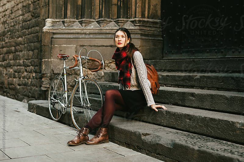 Chic woman sitting beside her vintage bicycle on the street. by BONNINSTUDIO for Stocksy United