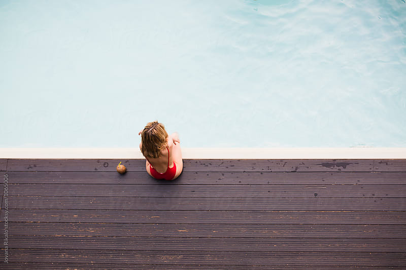 Young attractive woman sitting by the pool by Jovana Rikalo for Stocksy United
