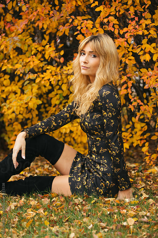 A beautiful blonde sitting up on the grass on a fall day looking back at the camera by Ania Boniecka for Stocksy United