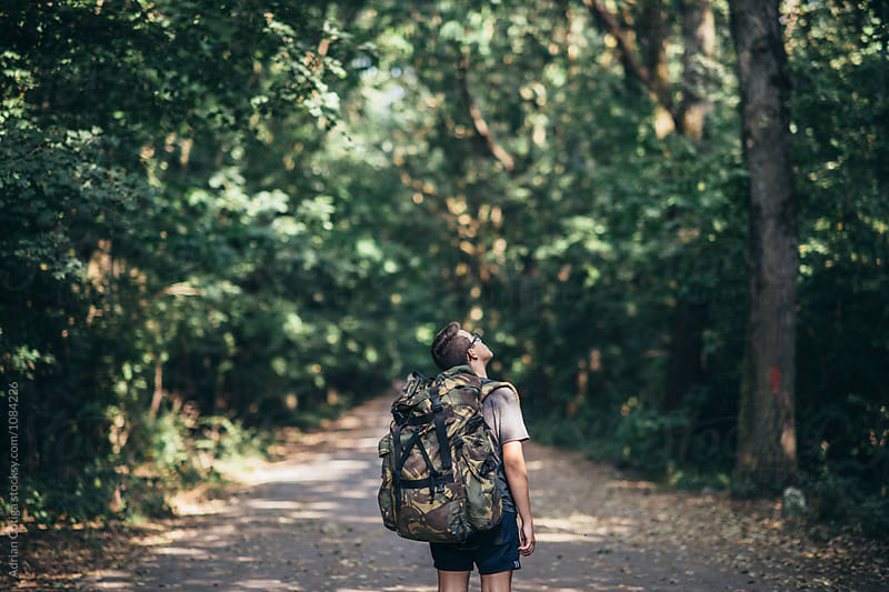 Young teen boy with a backpack exploring the forest by Adrian Cotiga for Stocksy United
