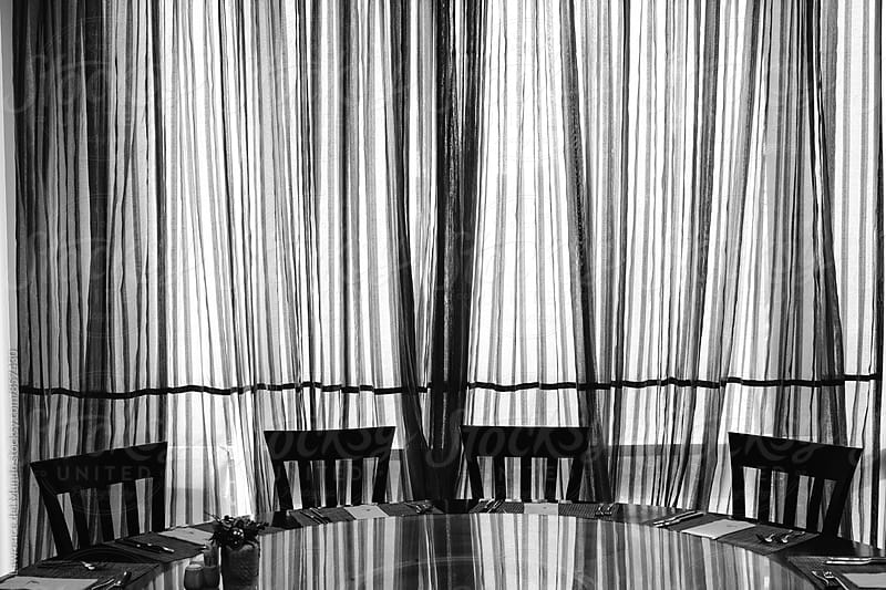 Silhouette image of chairs on a round table and curtain with line patterns in black and white by Lawrence del Mundo for Stocksy United