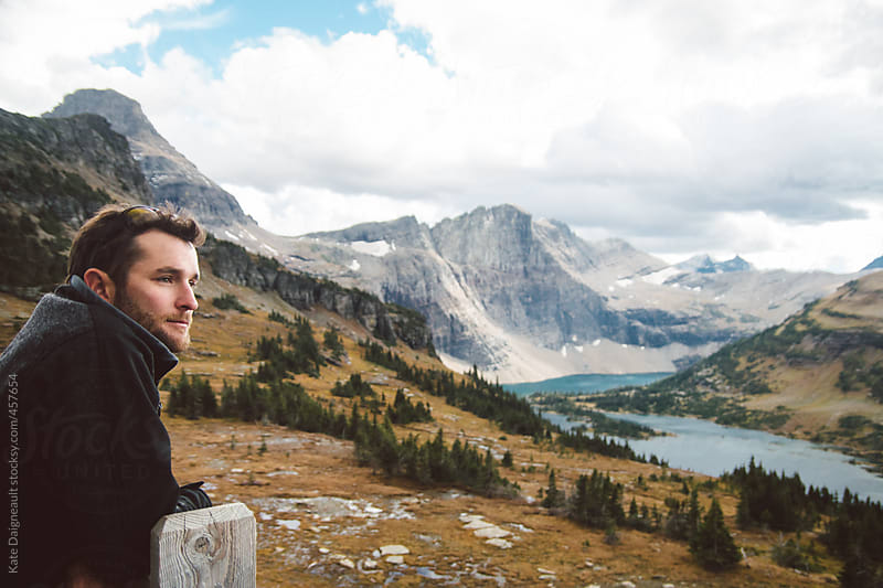 Man at overlook on Lost Lake trail in Glacier National Park by Kate Daigneault for Stocksy United
