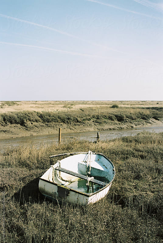 Boat in marshland at low tide. Morston Quay, Norfolk, UK. by Liam Grant for Stocksy United