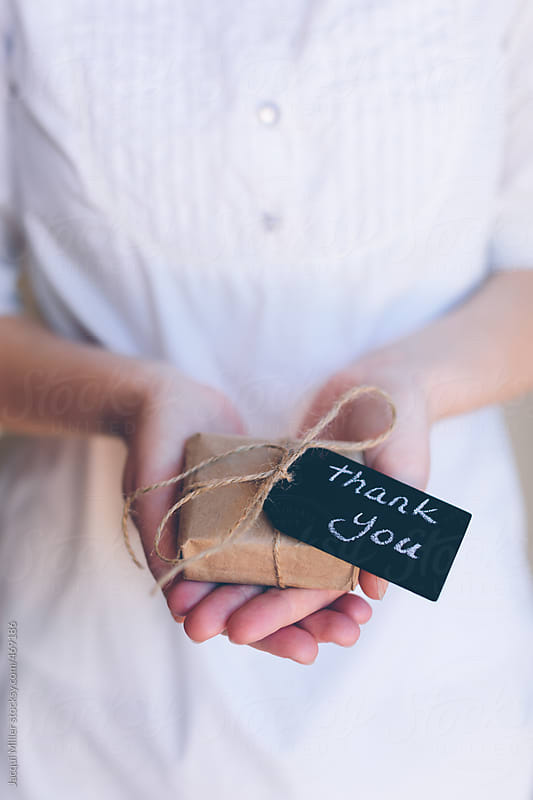Girls hands holding a small gift with a tag that says 'thank you' by Jacqui Miller for Stocksy United