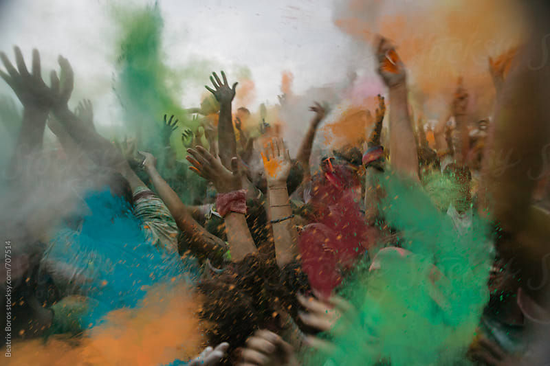 Burst of colors and happy crowd with hand up by Beatrix Boros for Stocksy United
