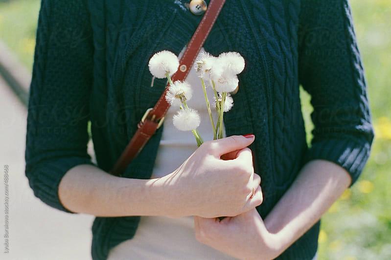Girl holding on dandelions in her hands by Lyuba Burakova for Stocksy United