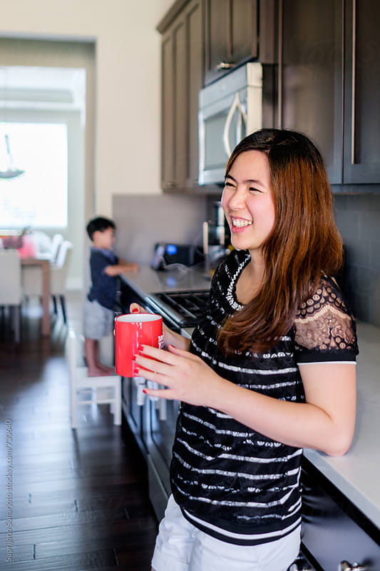 Asian woman holding a coffee mug while her son is watching on tablet in the background by Suprijono Suharjoto for Stocksy United