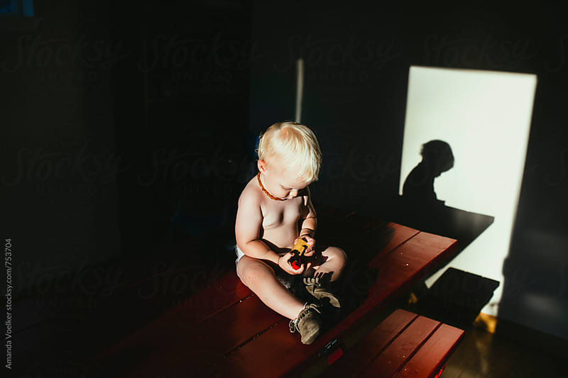 Little boy in direct light sits on kitcehn table looking at his toy train by Amanda Voelker for Stocksy United