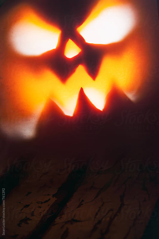 Halloween: Scary Pumpkin Face Glows With Evil Light by Sean Locke for Stocksy United