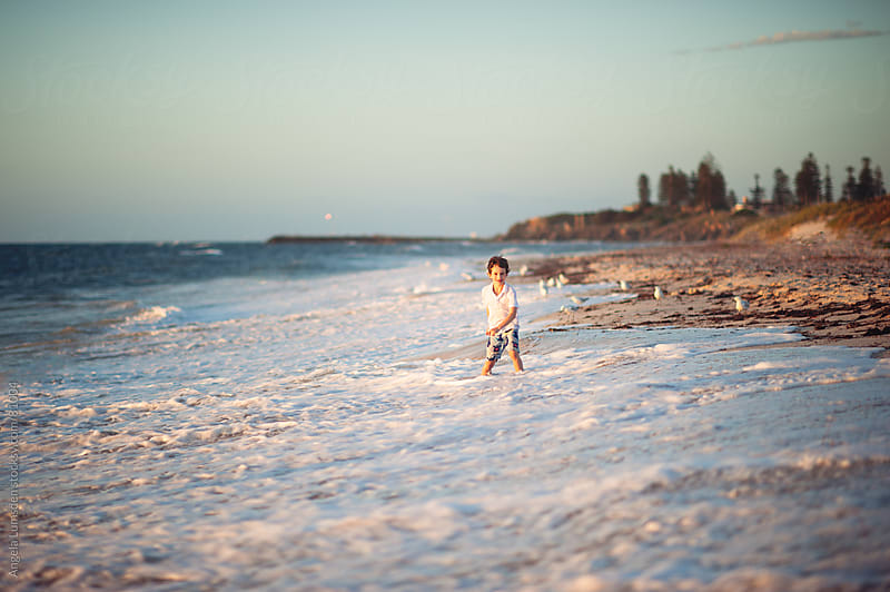 Boy playing in waves at the beach by Angela Lumsden for Stocksy United
