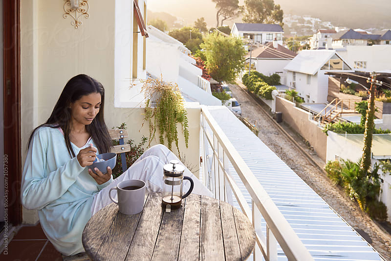 beautiful young woman eating breakfast outdoors  on the balcony by Daxiao Productions for Stocksy United