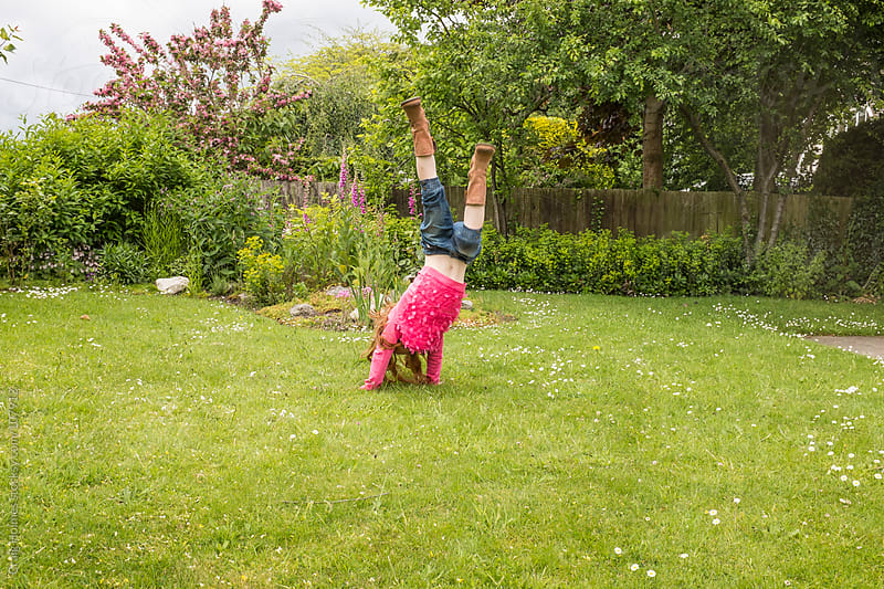 Girl doing a handstand in her garden by Craig Holmes for Stocksy United