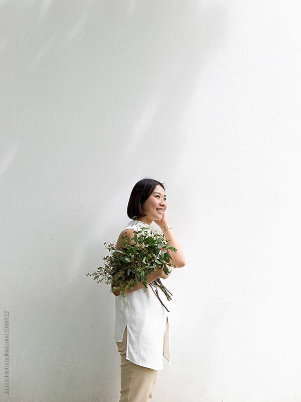 Girl in white shirt holding flowers by Sophia Hsin for Stocksy United
