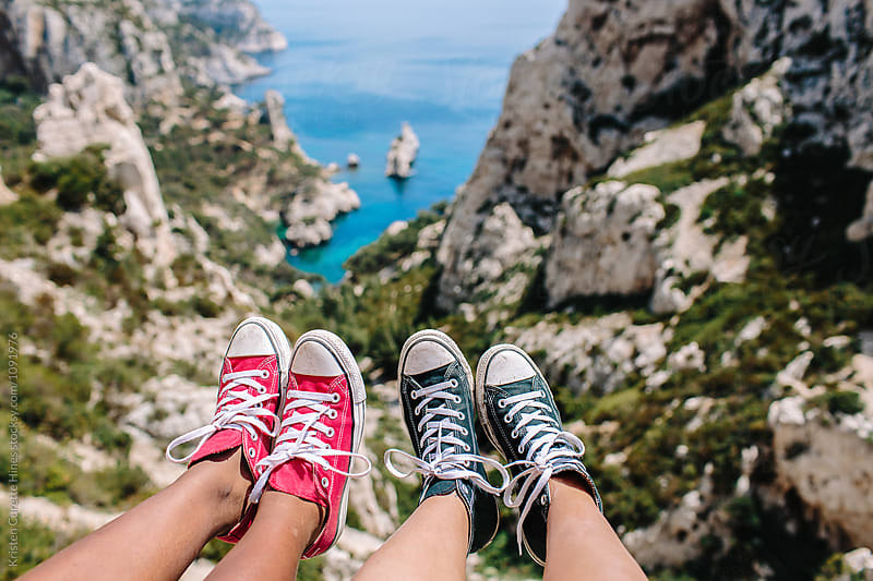 Two friends hanging their feet down towards cliffs / ocean coast by Kristen Curette Hines for Stocksy United
