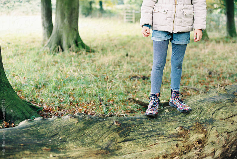 A little girl in flowery boots standing on a fallen tree. by Helen Rushbrook for Stocksy United