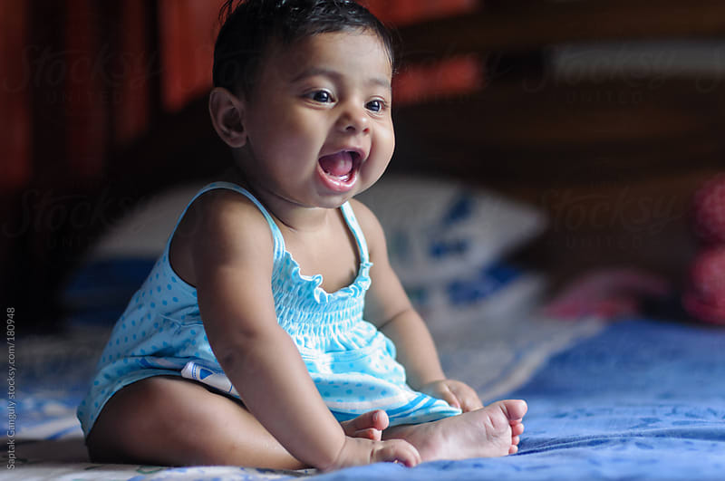 Cute baby girl sitting on bed and laughing by Saptak Ganguly for Stocksy United