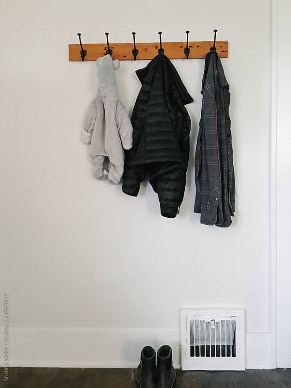 A families jackets hanging from a coat rack by Kristine Weilert for Stocksy United