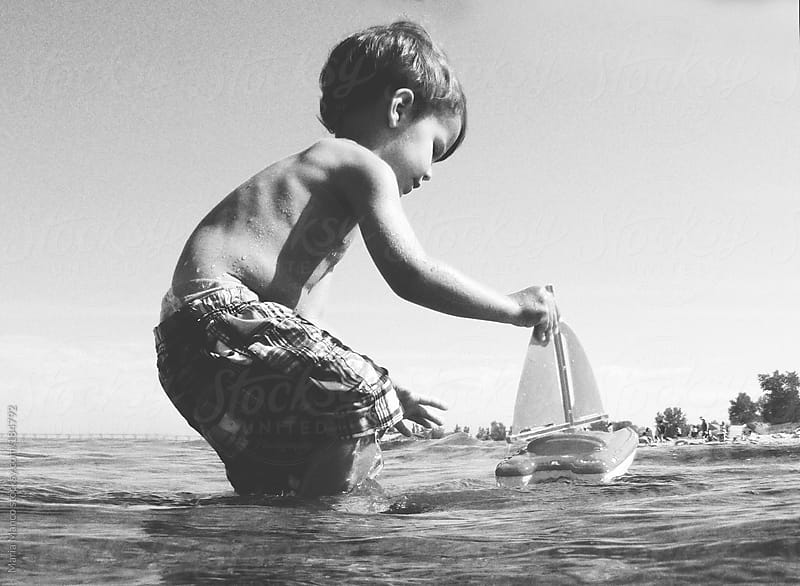 child sails toy boat in ocean by Maria Manco for Stocksy United