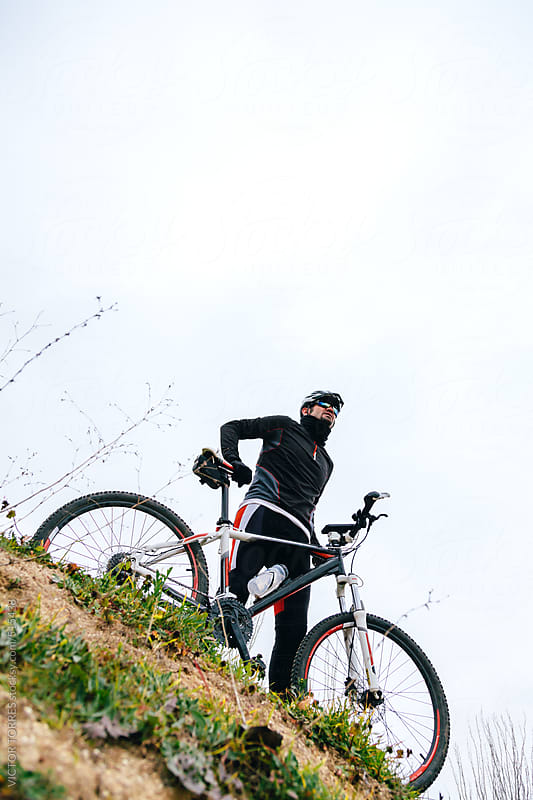 Mountain Bike Rider Resting Over a Hill by VICTOR TORRES for Stocksy United