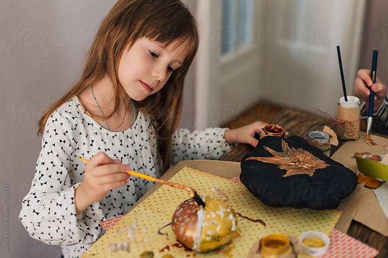Cute Girl Painting on a Pumpkin for Halloween by Lumina for Stocksy United