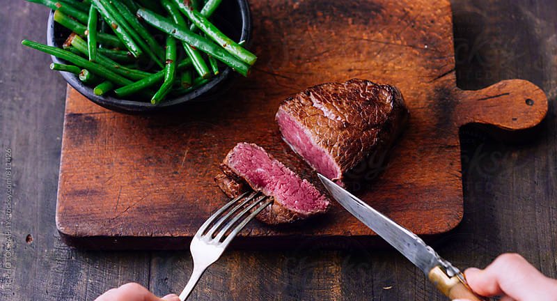 Slicing steak on cutting board by J.R. PHOTOGRAPHY for Stocksy United
