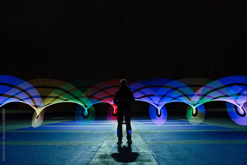 A single man silhouetted by rainbow swirls of light, standing in an empty car park by Maresa Smith for Stocksy United