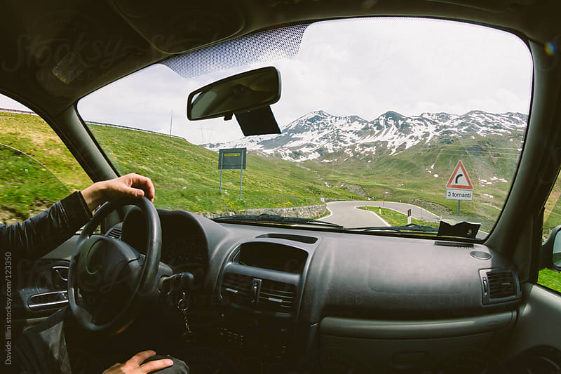 Driving a car on a mountain road by Davide Illini for Stocksy United