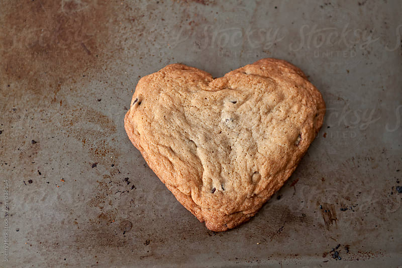 Heart shaped cookie on naturally distressed metal baking sheet by Sherry Heck for Stocksy United