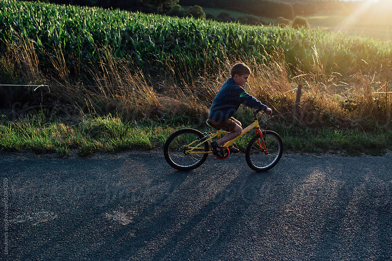 boy riding his bike by Léa Jones for Stocksy United