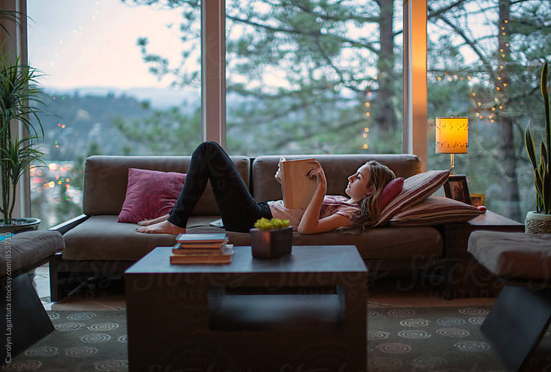 Teenage girl reading on the couch in a modern home by Carolyn Lagattuta for Stocksy United