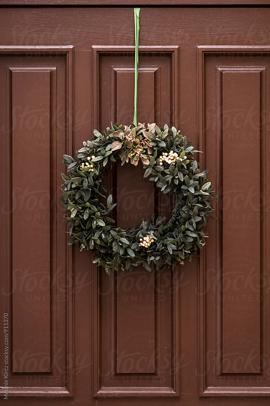 Wreath with white flowers on brown door by Melanie Kintz for Stocksy United