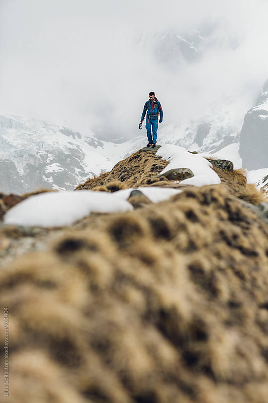 Young alpine climber with blue dress walking down from the viewpoint glacier in the Italian Alps by Jordi Rulló for Stocksy United