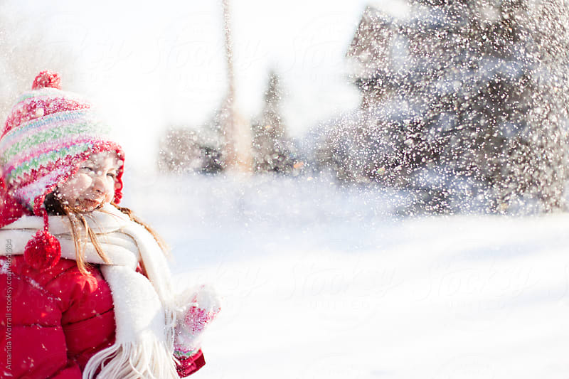 Happy young girl smiles as snow falls down on her by Amanda Worrall for Stocksy United