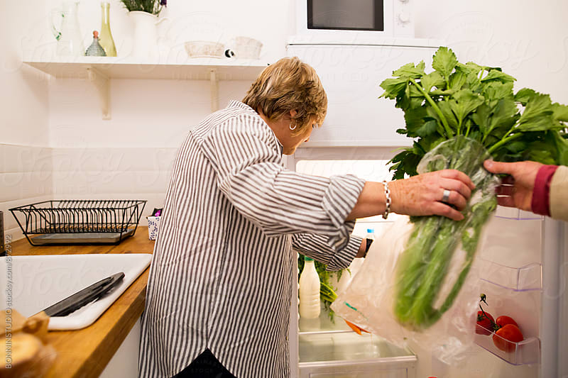 Elderly woman putting organic food into the fridge. by BONNINSTUDIO for Stocksy United