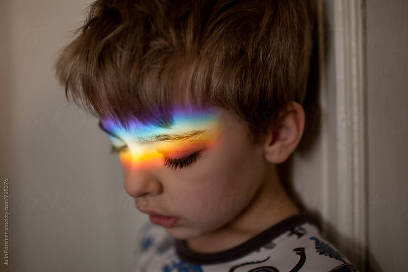 Boy looking down with rainbow on his eyes and forehead. by Julia Forsman for Stocksy United