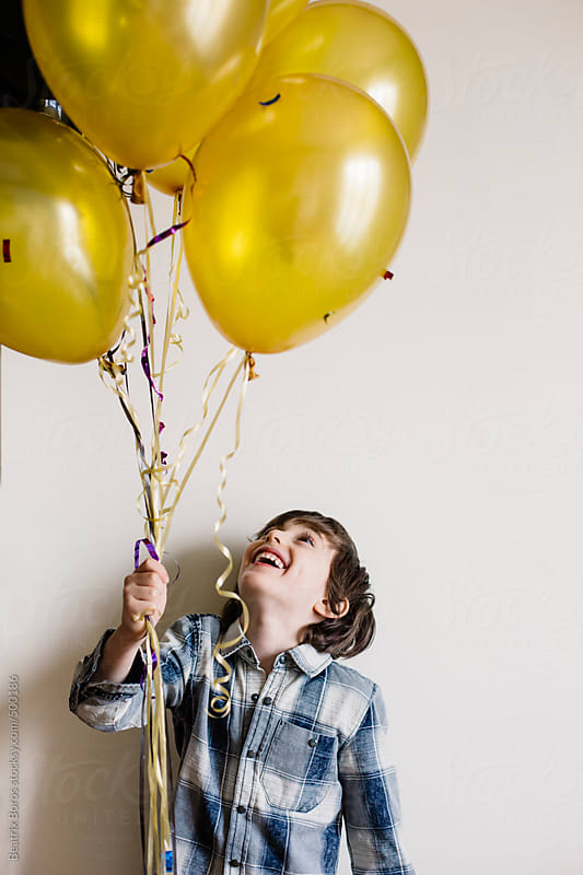 6 years old boy looking up at his golden and black balloons by Beatrix Boros for Stocksy United