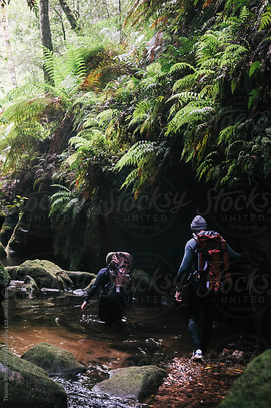 Friends walking through a wet canyon. by Thomas Pickard for Stocksy United