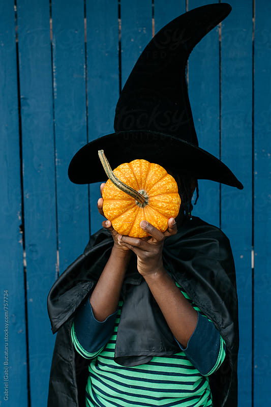 African American girl holding a pumpkin in front of her face by Gabriel (Gabi) Bucataru for Stocksy United