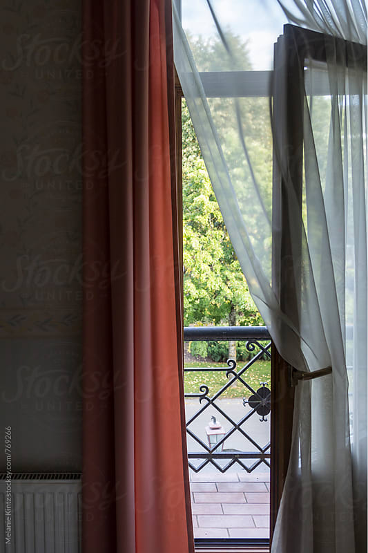 View from room with open balcony door by Melanie Kintz for Stocksy United