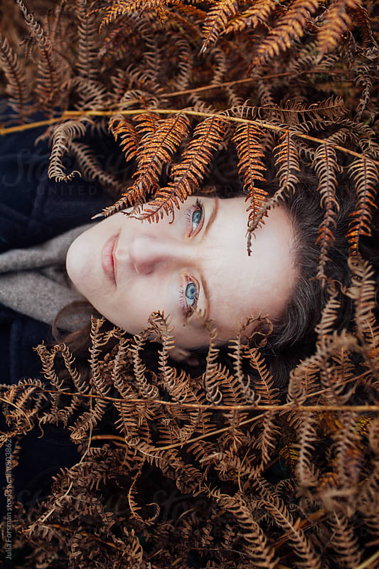 A pale woman with blue eyes lies in golden ferns. by Julia Forsman for Stocksy United